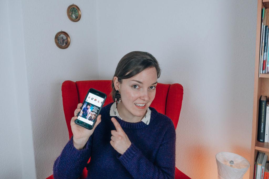 Frau sitzt in einem Sessel und hält ein Smartphone in die Kamera