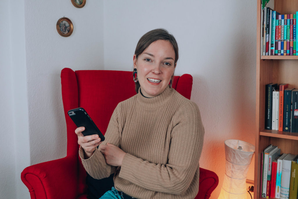 Frau mit Smartphone in der Hand in rotem Sessel