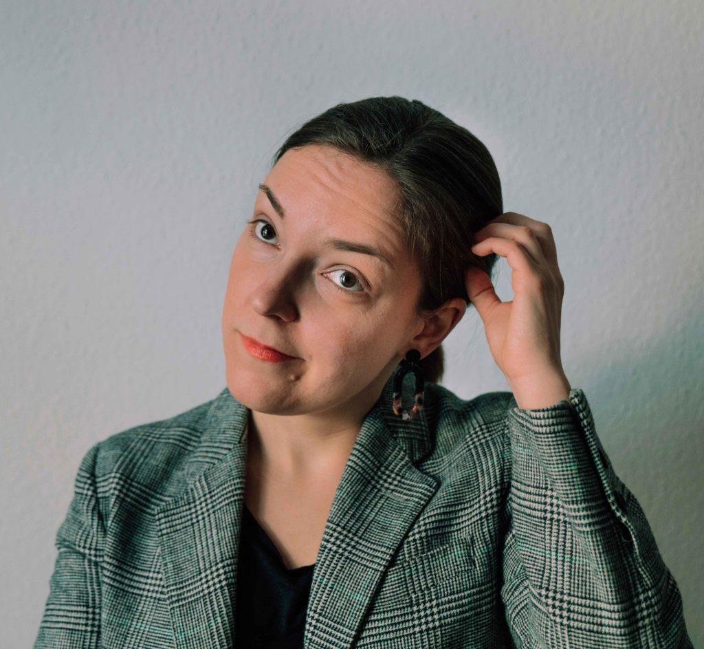 Portraitfoto: Frau im Blazer kratzt sich am Kopf