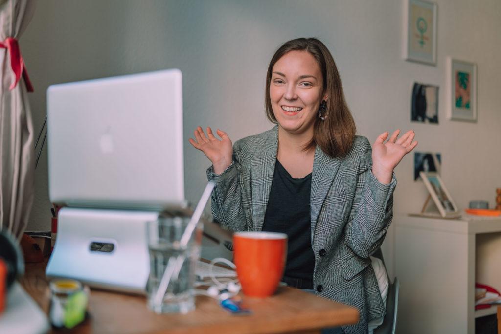 Frau vor Laptop mit ausgebreiteten Händen